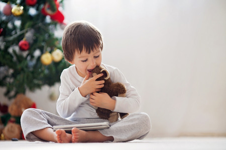 Cute little boy and his monkey toy, playing on tablet in front of a christmas tree