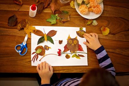 Lief kind, jongen, het aanbrengen van bladeren gebruik van lijm terwijl het doen van kunsten en ambachten in de school, de herfst de tijd Stockfoto