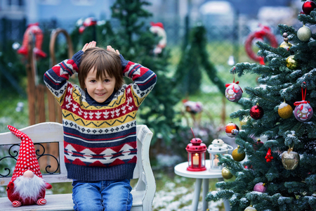Cute adorable child, boy, having fun outdoors in the garden on Christmas around the decorated christmas tree while snowing outside