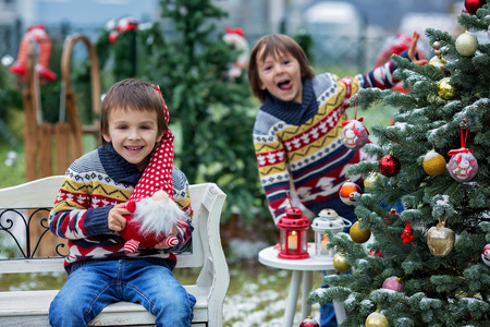 Two adorable children, boy brothers, having fun outdoors in the garden on Christmas around the decorated christmas tree while snowing outside Stock Photo