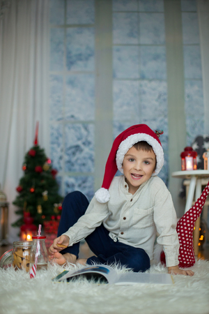 Cute preschool child, boy, reading a book and eating cookies at home, while snowing outdoors Stock Photo
