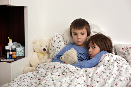 Two cute sick children, boys, staying in bed with fever, playing with teddy bear