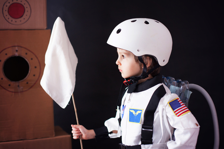 profession: Beautiful preschool boy, dressed as astronaut, with flag and carton rocket, proudly standing