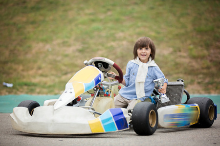 grand kid: Cute child, riding go cart, wins champion cup, happiness winner concept