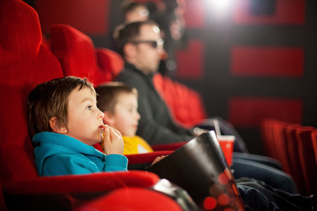 Father and two children, boys, watching cartoon movie in the cinema on 3D Stock Photo