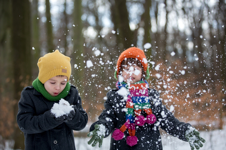 Happy little child, boy, playing outdoors in a snowy park, wintertime