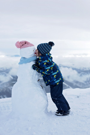 Cute child, building snowman and playing with it on top of mountain, wintertime