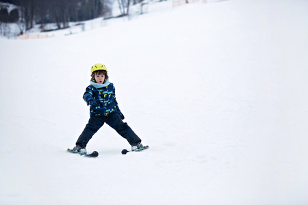 Cute child, skiing in the mountain, wintertime