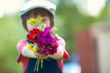 Preschool child, holding bouquet of wild flowers, gathered for mom. Mothers day concept