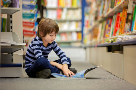 Adorable little child, boy, sitting in a book store, reading books Imagens
