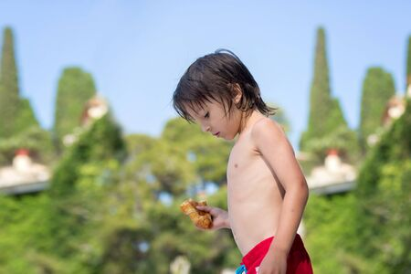 Cute child,  boy, eating croissant on the beach, French Riviera