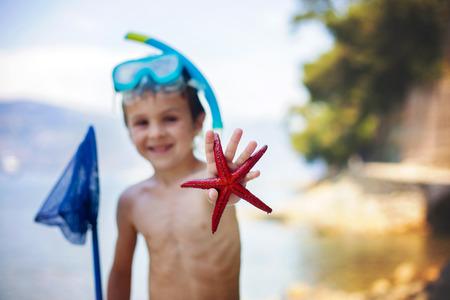 plancton: Niño pequeño que sostiene las estrellas de mar de cinco puntos rojos y la red en sus manos en la playa