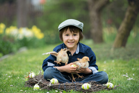Cute little preschool child, boy, playing with easter eggs and chicks in spring blooming garden, sitting in handmade nest, easter happiness childhood concept Stock Photo