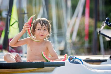 かわいい小さな子供、少年、ビーチでスイカを食べる夏