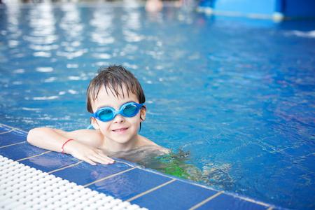 甘い子供、少年、楽しんで観光スポット、休日に大きなスイミング プールで泳いで水世界の遊び場で遊ぶ