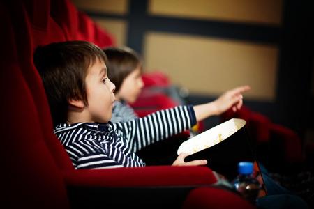 두 유치원 어린이, 쌍둥이 형제, 영화관에서 영화보기, 팝콘 먹기 스톡 콘텐츠