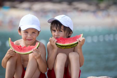 2 つのほとんどの子供、少年兄弟、ビーチでスイカを食べる夏 写真素材