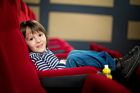 taker: Two preschool children, twin brothers, watching movie in the cinema, eating popcorn