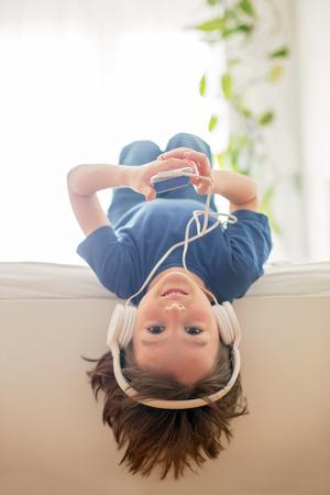 Leuke jongen met telefoon en hoofdtelefoons, muziek luisteren, binnenshuis, liggend in de slaapkamer