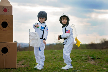 Two adorable children, boy brothers, playing in park on sunset, dressed like astronauts, imagining they are flying on the moon Stock Photo