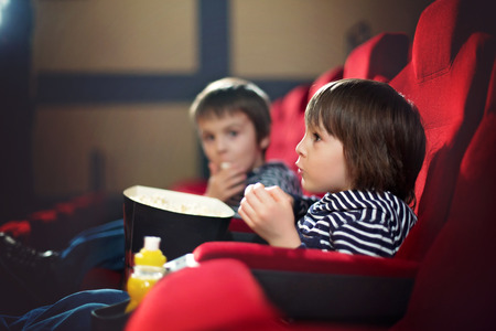 Two preschool children, twin brothers, watching movie in the cinema, eating popcorn
