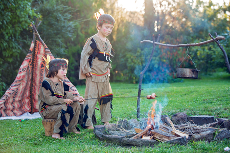outdoor fireplace: Cute portrait of native american boys with costumes, playing outdoor around fire on sunset, preparing sausages, summertime