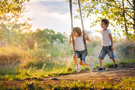 Two children, boy brothers, having fun on a swing in the backyard on sunset Stock Photo