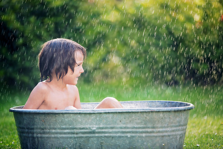 Two children, boy brothers, having a bath outdoors, making soap bubbles, summertime Stock Photo