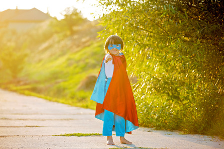 Cute sweet little preschool child, boy, playing superhero on a rural path in a small village on sunset, summertime Stock Photo