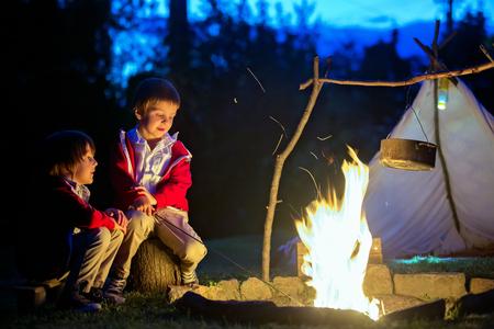 Twee zoete jongens, die na het zonsondergang rond het kampvuur zitten, luisterende eng verhalen Stockfoto