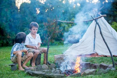 二人の甘い子供男の子兄弟、日没の夏キャンプ、ポテトを食べる