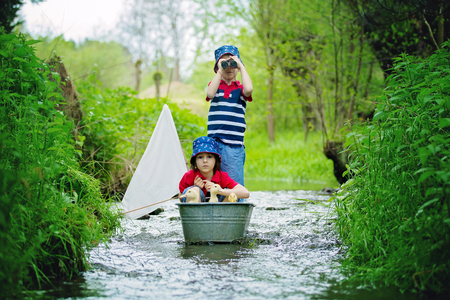 Cute children, boy brothers, playing with boat and ducks on a little river, sailing and boathing. Kid having fun, childhood happiness concept