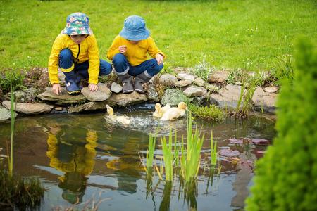 雨の中、小さなアヒルの子と一緒に遊んでの美しい子供、夏