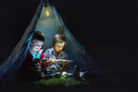 Cute little brothers, playing on tablet and telephone at night in campside, in the tent Banco de Imagens