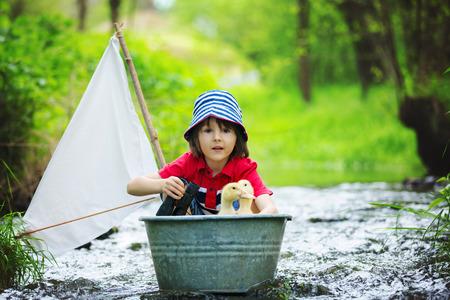 Schattig kind, jongen, spelen met boot en eenden op een kleine rivier, zeilen en varen. Kind met plezier, jeugd geluk concept Stockfoto