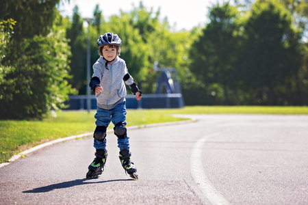 Cute little child, boy, riding on a skating  in the park, springtime Stock Photo