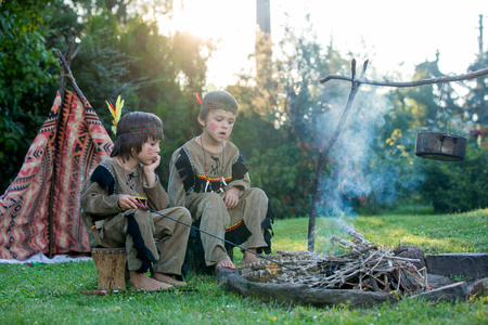 Cute portrait of native american boys with costumes, playing outdoor around fire on sunset, preparing sausages, summertime