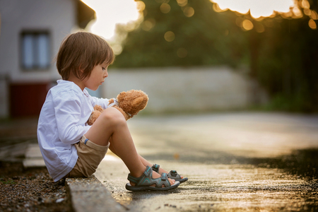 Sad little boy, sitting on the street in the rain, hugging his teddy bear, summertime on sunset