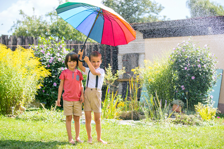 Two adorable children, boy brothers, playing with colorful umbrella under sprinkling water in their backyard Stock Photo