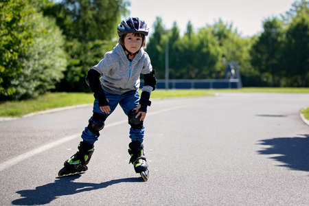 Cute little child, boy, riding on a rollerblades in the park, springtime