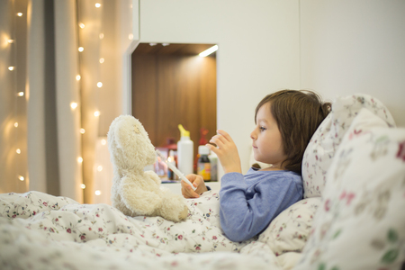 Cute sick child, boy, staying in bed, playing with teddy bear, giving him medicine and checking for fever Stock Photo