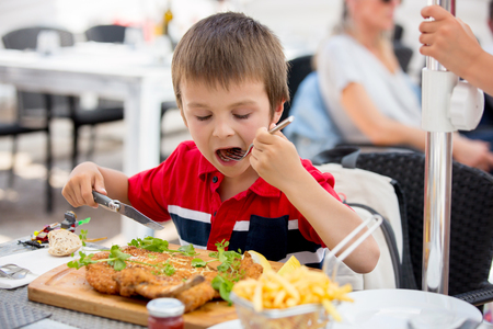Preschool child, eating big steak of meat and french fries at a restaurant