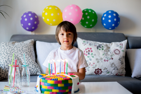 Sweet little child, boy, celebrating his sixth birthday, cake, balloons, candles, cookies. Childhood happiness concept Stock Photo