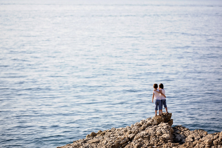 Twee kinderen, die op rotsen aan de kust van de zee staan, kijken naar de passerende boten