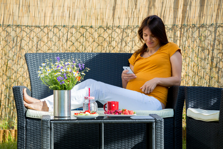 unborn: Young pregnant woman, having healthy breakfast, coffee, fruits and reading a book in a backyard garden Stock Photo