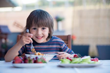 Cute child, preschool boy, eating spaghetti for lunch outdoors in garden, summertime 版權商用圖片 - 80537237