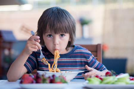Leuk kind, peuterjongen, die spaghetti voor lunch in openlucht in tuin eten, zomer