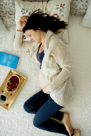 Young pregnant woman, lying in bed with smart phone, book, coffee and fruits, motherhood concept
