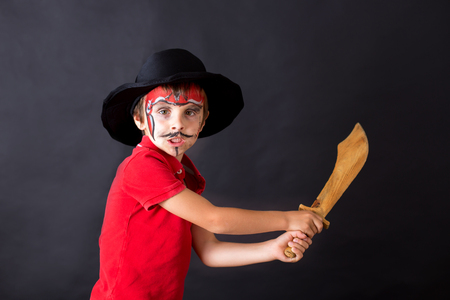 Cute school boy, playing games, painted as pirate, holding sword, isolated images on black background