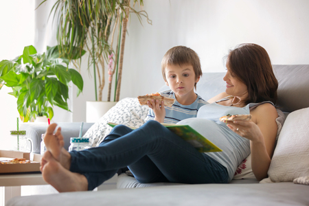 Happy young family, pregnant mother and boy, eating tasty pizza at home, sitting on the sofa, reading a book and having a laugh
